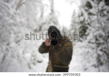 Closeup shot of a muzzle of hunter rifle, man is aiming it to camera in winter forest. - stock photo