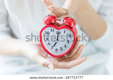 Closeup shot of a woman holding red heartshape alarm clock. Time set at 7.00 am.  Close up of female hands holding a red alarm clock. Shallow depth of field with focus on the alarm clock.