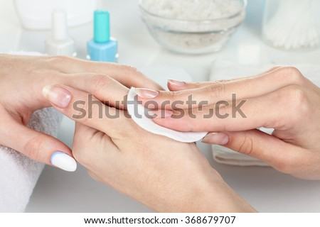Closeup shot of a woman in a nail salon receiving a manicure by a beautician with cotton wool with acetone. Woman getting nail manicure. Beautician file nails to a customer. - stock photo