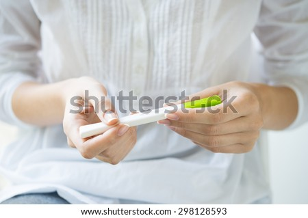 Closeup shot of a woman looking at pregnancy test. She's is checking her pregnancy exam. Detail hands of a girl holding pregnancy test. Shallow depth of field with focus on pregnancy test.