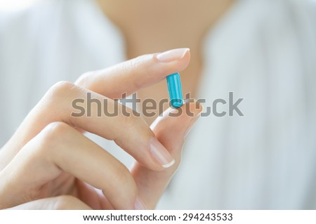 Closeup shot of a woman showing blue capsule pill. Female hand holding a medicine. Shallow depth of field with focus on blue capsule pill.