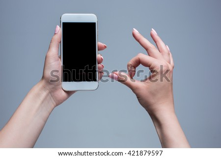 Closeup shot of a woman typing on mobile phone on gray background. Female hands holding a modern smartphone and pointing with figer. Blank screen to put it on your own webpage or message. - stock photo