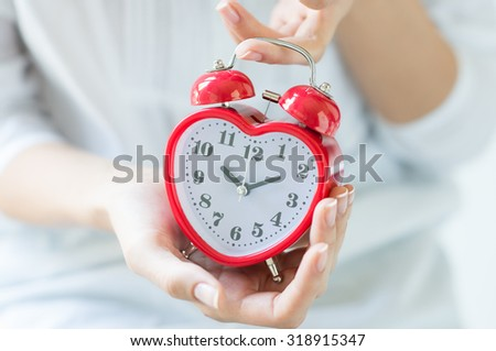 Closeup shot of a woman with white shirt holding red heartshape alarm clock indoor. Female hands holding alarmclock.  Shallow depth of field with focus on the alarm clock.  - stock photo