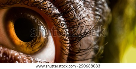Closeup shot of an human eye with some green blurry background. The pupil of the eye is captured very big. - stock photo