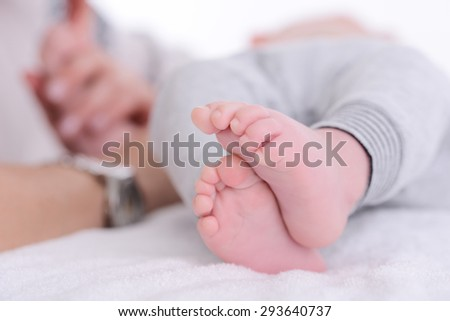 closeup shot of baby foot laying down on a white blanket - stock photo