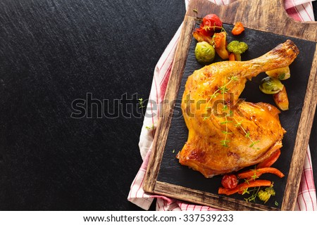 Closeup shot of baked chicken leg with thyme and vegetables on slate. - stock photo