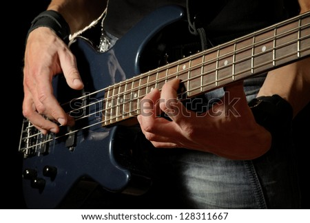 closeup shot of bass guitar in hands of musician - stock photo