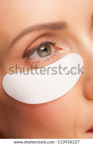 Closeup shot of beautiful woman applying gel eye mask. Middle Aged, beauty treatment - stock photo