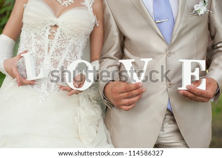 Closeup shot of bride and groom hands holding the word Love - stock photo