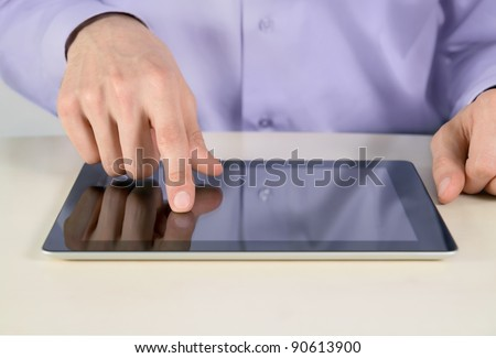 Closeup shot of businessman hands are touching on contemporary generic tablet pc. Shallow depth of field on finger. - stock photo