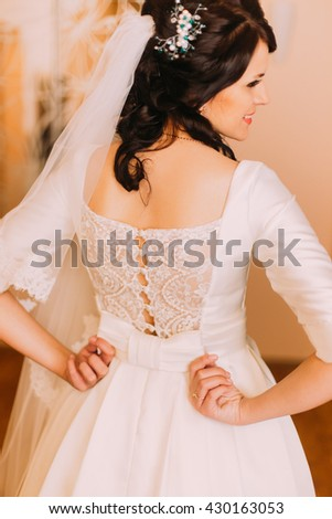 Closeup shot of elegant, brunette bride in vintage white dress fixing her dressing before wedding. Back view - stock photo
