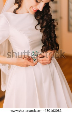 Closeup shot of elegant, brunette bride in vintage white dress fixing her dressing before wedding - stock photo
