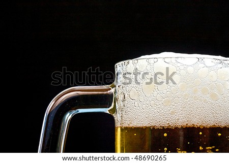 Closeup shot of Fresh cold golden light beer with froth served in a glass pint mug on black background - stock photo