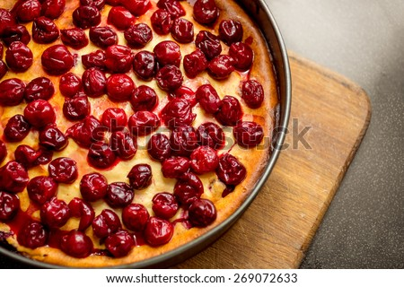 Closeup shot of freshly baked pie decorated by cherries on wooden board - stock photo