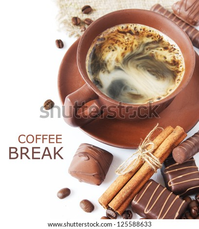 Closeup shot of freshly prepared cup of coffee with cinnamon, coffee beans, chocolate candy and cakes isolated on white background (with sample text) - stock photo
