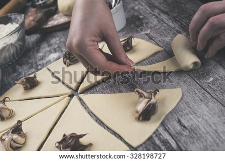 Closeup shot of gently young woman hands making a beautiful and delicious homemade rolls with nougat creme. Processed to mach old film look. - stock photo