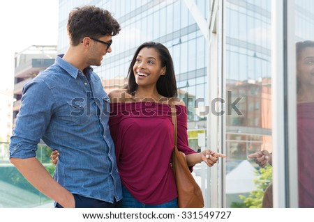 Closeup shot of happy couple looking at each other and smiling. Happy woman pointing the shop window with her boyfriend. Happy smiling man and woman doing shopping in the city center. A couple walking. - stock photo