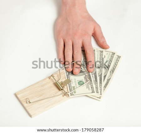 Closeup shot of man got caught in mouse trap with dollar bait - stock photo