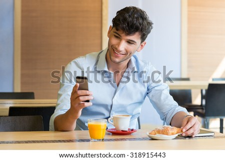 Closeup shot of man texting on mobilephone at caf���©. Guy is doing breakfast at coffee bar. Young man looking at smartphone and smiling during breakfast.  - stock photo