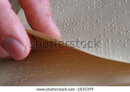 closeup shot of someone turning a Braille book page - stock photo
