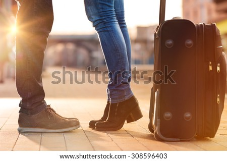 Closeup shot of woman feet standing on tiptoe while embracing her man at railway platform for a farewell before train departure. A travelling luggage is on the foreground. - stock photo