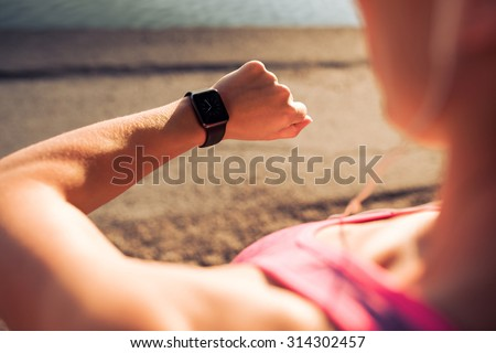 Closeup shot of young female jogger ready to run set and looking at sports smartwatch. Fitness woman checking her performance. - stock photo