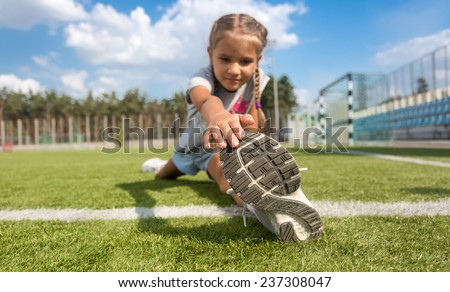 Closeup shot of young girl stretching legs on soccer field at sunny day - stock photo
