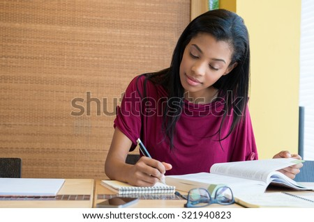 Closeup shot of young woman taking down note in diary. Female student preparing note for the exam. Concentrated girl studying on a book and taking down note sitting at the desk. - stock photo