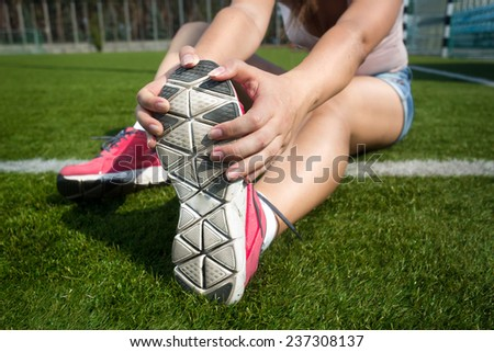 Closeup shot of young woman warming up on grass before running - stock photo