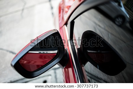 Closeup side rear-view mirror on a modern red car - stock photo