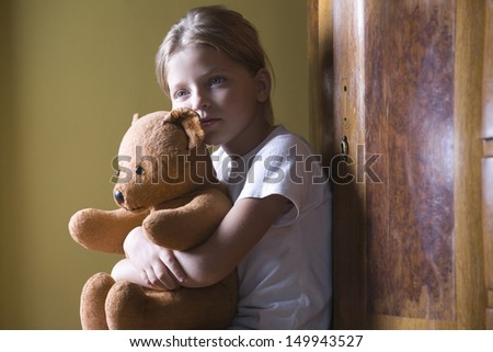 Closeup side view of a little girl embracing her teddy bear - stock photo