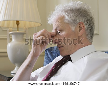 Closeup side view of a middle aged businessman pinching bridge of nose on couch - stock photo