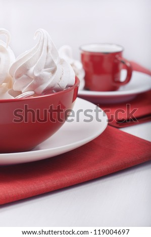 Closeup side view of a red bowl with meringues and away the red cup on the red rag towels. - stock photo