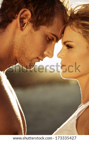 Closeup side view of a romantic young couple on the beach - stock photo