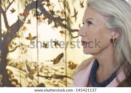 Closeup side view of a serious senior woman against screen - stock photo