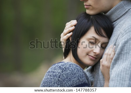 Closeup side view of a young woman laying head on man's chest against blurred background - stock photo