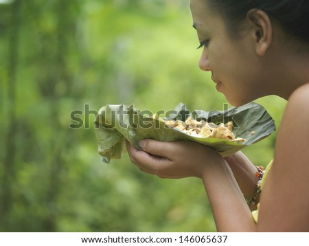 Closeup side view of a young woman smelling food on leaf against blurred green background - stock photo