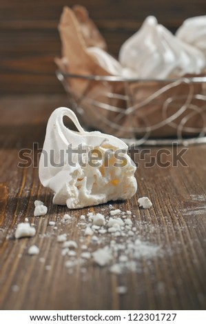 Closeup side view of broken meringue with crumbs and lot of meringues in iron bowl on dark wooden background - stock photo