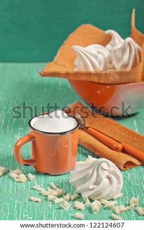 Closeup side view of meringue, orange mug with milk foam, two spoons on textile napkin on green cracked background - stock photo