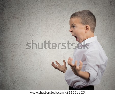 Closeup side view Portrait Angry Child Screaming fists up in air isolated grey wall background. Negative Human face Expression Emotion Reaction Perception. body language Conflict confrontation concept - stock photo