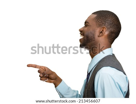 Closeup side view portrait happy young man, laughing, pointing with finger at someone, something, isolated white background. Positive human face expressions, emotions, feelings, attitude, approach - stock photo