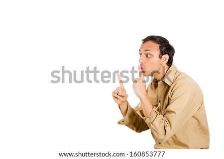 Closeup side view profile portrait of handsome man  in brown shirt placing fingers on lips as if to say shhh and pointing with other hand, isolated on white background with copy space - stock photo