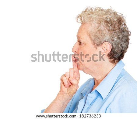 Closeup side view profile portrait of senior mature woman placing fingers on lips with shhh sign symbol, isolated on white background. Negative emotion facial expression feelings, body language - stock photo