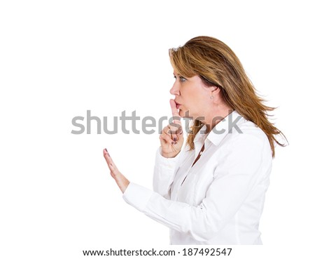Closeup side view profile portrait, pretty, middle age woman placing fingers on lips with shhh sign symbol, isolated white background. Negative emotion facial expression feelings, body language - stock photo