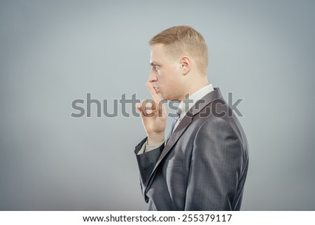 Closeup side view profile portrait, serious young man in shirt, tie placing fingers on lips with shhh, isolated gray background. Negative emotio - stock photo