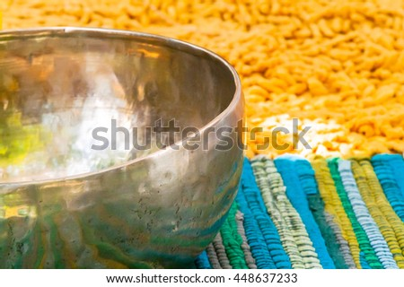 closeup singing bowl on a mat on the nature - stock photo