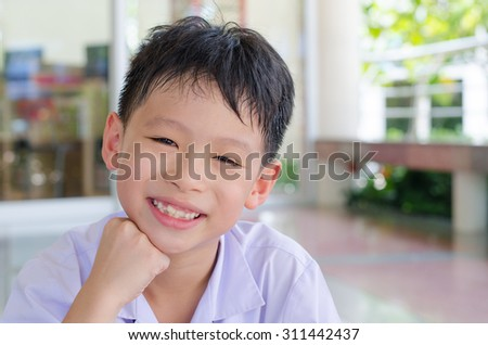 Closeup smiling Asian student face looking at camera - stock photo