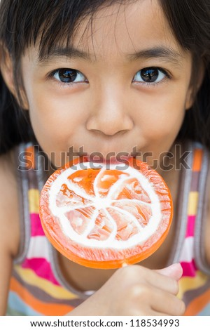 Closeup smiling little girl with a lollipop - stock photo