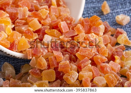 Closeup spilled bowl of dehydrated diced Carica papaya cubes on blue fabric placemat - stock photo