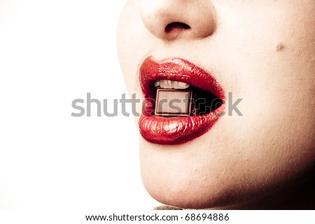 Closeup studio portrait of young female model with makeup and bright red lipstick eating a piece of non-branded chocolate and holding it in her mouth - stock photo
